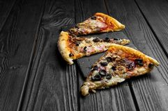 Pieces of pizza on dark black board, traditional italian pizza royalty free stock photography