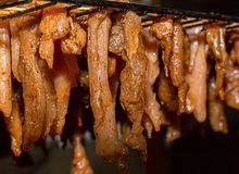 Pieces of pork and chicken meat in spices hang, preparation for drying of sharp chips. Nutritious snack Stock Photography