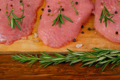 Pieces of pork on the cutting board, salt, spicy herbs Stock Photos