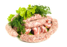 Pieces of Pork meat and Sausages. Isolated over white Stock Images