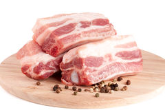 Pieces of pork with peppercorn on a cutting board isolated on white background Stock Photos