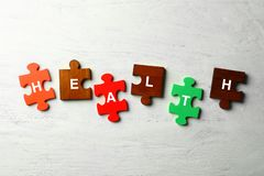 Pieces of puzzle composed word HEALTH on white wooden background stock photography