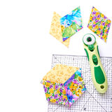 Pieces of quilt with rotary knife and ruler on white surface Stock Photos