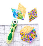 Pieces of quilt with rotary knife and ruler on white surface Royalty Free Stock Image