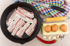 Pieces of raw bacon in cast iron frying pan, eggs Stock Photography