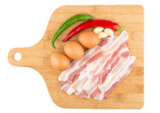 Pieces of raw bacon, eggs and chili peppers on board Stock Image