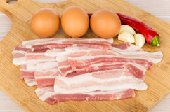 Pieces of raw bacon, eggs and chili peppers on board Royalty Free Stock Image