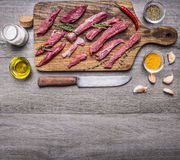 pieces  raw beef on a cutting board with a knife, butter and seasonings, border, with text area on wooden rustic background top v Royalty Free Stock Photos