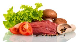 Pieces of raw beef, tomato pieces, mushrooms, lettuce, and scoop. With pepper  on white background Stock Photography