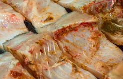 Pieces of raw fish in oil. Pieces of carp fish in oil ready for cooking with spices Stock Photo
