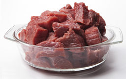 Pieces of raw meat in a bowl. Cut pieces of raw meat in a glass bowl on the white background Stock Photography