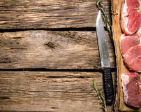 Pieces of raw meat with a butcher knife. Royalty Free Stock Image