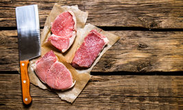 Pieces of raw meat with a butcher knife. Royalty Free Stock Photography