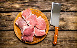 Pieces of raw meat with knife on cutting Board. On a wooden table. Top view Stock Photo