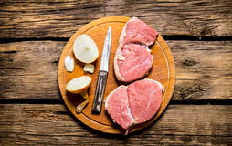 Pieces of raw meat with onions. On a chopping Board. On a wooden table. Top view Stock Images