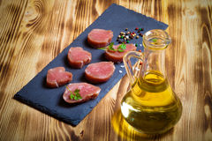 Pieces of raw meat on a plate of slate herbs spices and olive oi. L on a new burned wooden background. Toned Royalty Free Stock Photo
