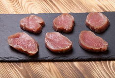 Pieces of raw meat on a plate of slate on a new burned wooden ba. Ckground. Selective focus Royalty Free Stock Photo