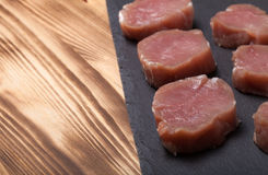 Pieces of raw meat on a plate of slate on a new burned wooden ba. Ckground. Selective focus Stock Photo