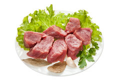 Pieces of raw meat on a white plate is isolated on a white backg Royalty Free Stock Image