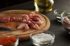Pieces of raw meat on wooden cutting board with spices and bottle of oil. Cooking process for recipe Royalty Free Stock Photo