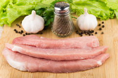 Pieces of raw pork on board, greens, garlic Stock Image
