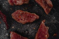 Pieces of raw pork medalions steak with spices, salt and pepper on a dark baton background in rustic style, top view stock photography