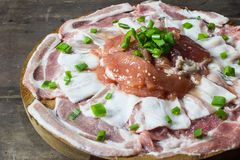 Pieces of raw pork with onion leafs Stock Images