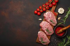 Pieces of raw pork steak with basil, cherry tomatoes, rosemary, garlic, pepper, salt and spice mortar on cutting board and rusty royalty free stock photo