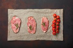Pieces of raw pork steak on culinary paper with cherry tomatoes, rosemary and red pepper on rusty brown background royalty free stock images