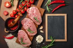 Pieces of raw pork steak on cutting board with cherry tomatoes, rosemary, garlic, pepper, salt and spice mortar and chalk board on royalty free stock image