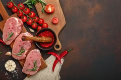 Pieces of raw pork steak on cutting board with cherry tomatoes, rosemary, garlic, pepper, salt and spice mortar on rusty brown royalty free stock images
