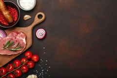 Pieces of raw pork steak on cutting board with cherry tomatoes, rosemary, garlic, red pepper, onion, salt and spice mortar on royalty free stock photo