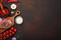 Pieces of raw pork steak on cutting board with cherry tomatoes, rosemary, garlic, red pepper, onion, salt and spice royalty free stock image