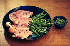 Pieces of raw pork steak and ingredients on a black plate. Pieces of raw pork steak with spices and herbs rosemary Stock Photos