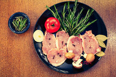 Pieces of raw pork steak and ingredients on a black plate Royalty Free Stock Photos