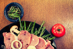 Pieces of raw pork steak and ingredients on a black plate Royalty Free Stock Photography