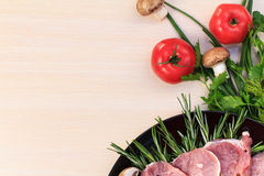 Pieces of raw pork steak and ingredients on a black plate Stock Image