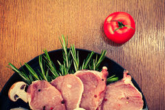 Pieces of raw pork steak and ingredients on a black plate Royalty Free Stock Images
