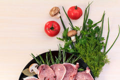 Pieces of raw pork steak and ingredients on a black plate. Pieces of raw pork steak with spices and herbs rosemary Royalty Free Stock Photo