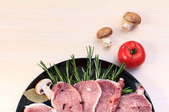 Pieces of raw pork steak and ingredients on a black plate. Pieces of raw pork steak with spices and herbs rosemary Royalty Free Stock Images