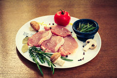 Pieces of raw pork steak and ingredients on a white plate. Pieces of raw pork steak with spices and herbs rosemary Royalty Free Stock Image