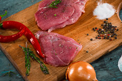 Pieces of raw pork steak with spices and herbs rosemary. Pieces of raw pork steak with spices and herbs, salt and pepper on a wooden background in rustic style Stock Photo