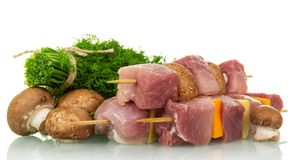 Pieces of raw pork, vegetables on wooden skewers and mushrooms,. Dill isolated on white background Stock Photography