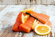 Pieces of raw salmon. With lemon slices surrounded by rustic background Stock Images