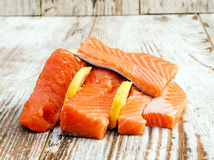 Pieces of raw salmon. With lemon slices surrounded by rustic background Royalty Free Stock Images