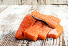 Pieces of raw salmon. Surrounded by rustic background Stock Image
