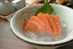 Pieces of raw Salmon on ice, Sashimi served with ice in a beautiful japanese bowl. Closed-up raw salmon fish, a top famous Japanese food. The taste is Stock Image