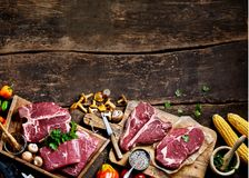 Pieces of raw steak prepared on wooden board. Pieces of raw steak prepared on cutting board among mushrooms, corn, peppers against wooden background stock photos