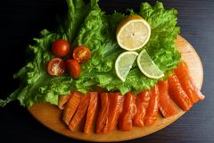 Pieces of red fish with lemon and cherry tomatoes on a wooden board stock image