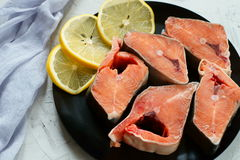 Pieces of red fish with lemon. Pieces of red fish - pink salmon with lemon on a black plate Royalty Free Stock Photography